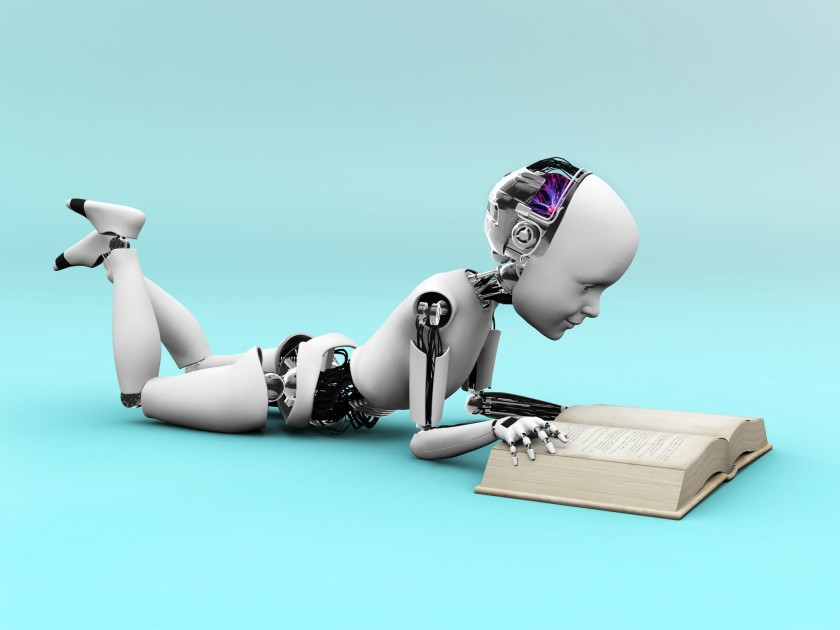 Android or robot lying down reading a big open book