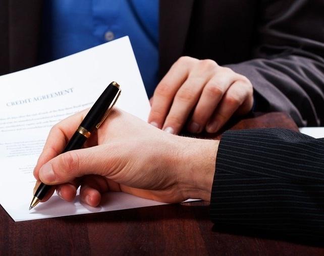 A closeup of a man signing an express cash loan agreement-1-133531-edited