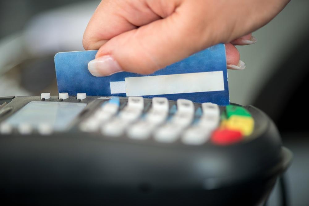Hand swiping debit card on pos terminal.jpeg
