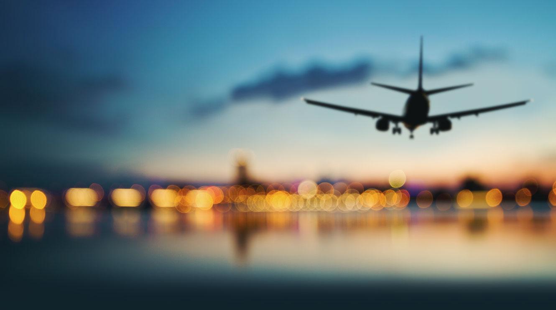 Image of passenger jet landing at an airport at dusk