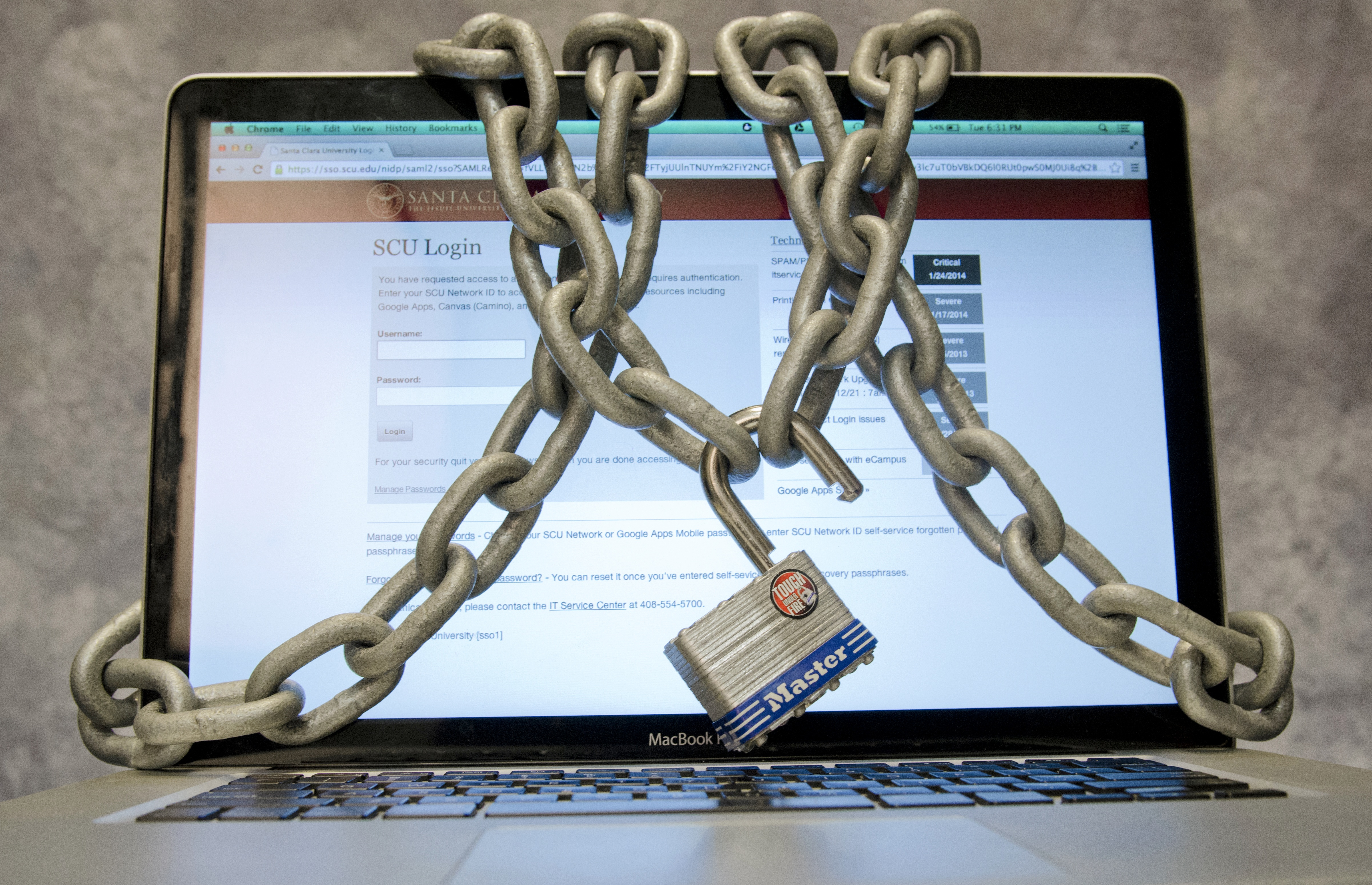 Laptop open onto a login screen with chains and padlock wrapped around it