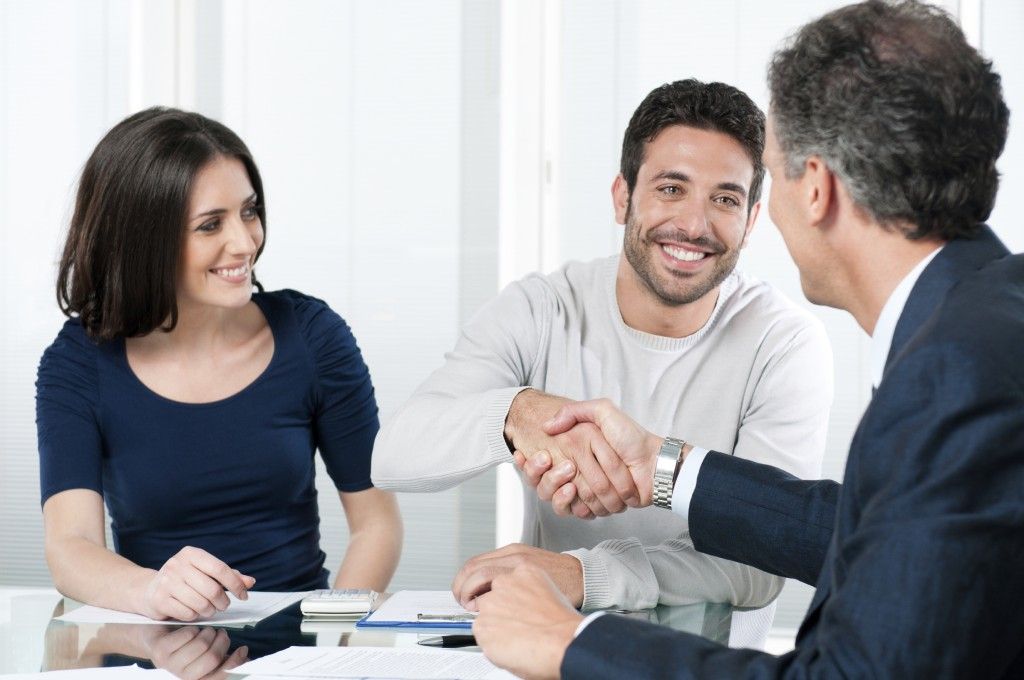 Young couple at a meeting table shaking hands with a businessman signing documents